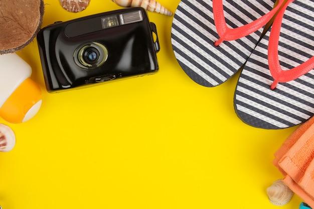 Zomeraccessoires met schelpen, slippers, een camera op een felgele achtergrond. bovenaanzicht.