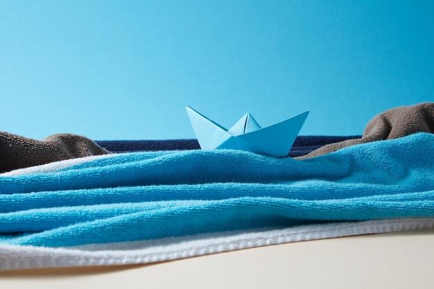 Zomerachtergrond handgemaakt van kleurrijke handdoeken met ambachtelijk schip op een papieren lucht en zand.