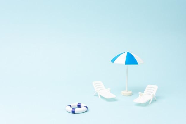 Zomerachtergrond met ligbedden, parasol en zwemring op pastelblauwe achtergrond