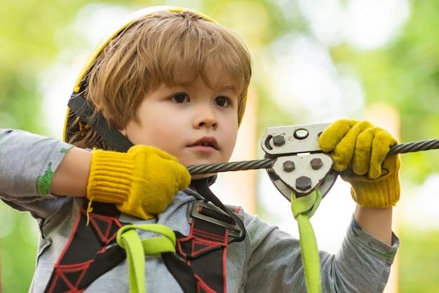 Zomeractiviteiten voor kinderen. portret van een mooi jong geitje op een touwpark tussen bomen. elke kindertijd
