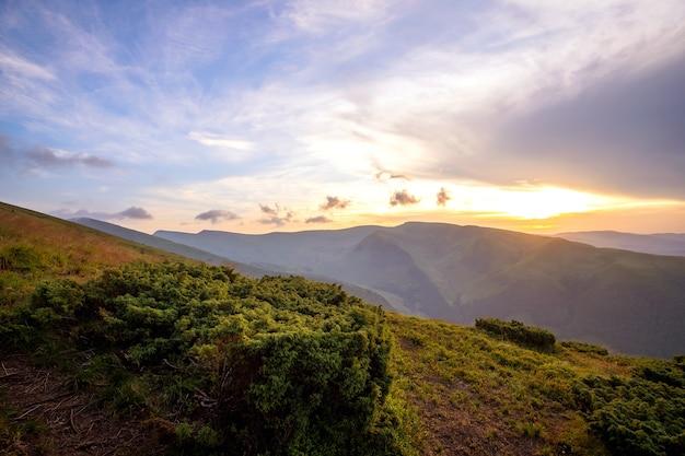 Zomeravond berglandschap met met gras begroeide heuvels en verre toppen bij kleurrijke zonsondergang. Premium Foto