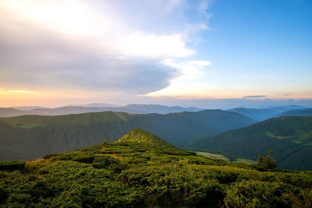 Zomeravond berglandschap met met gras begroeide heuvels en verre toppen bij kleurrijke zonsondergang.