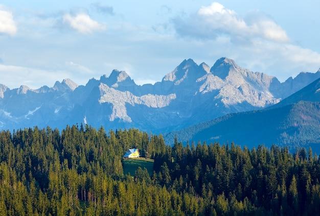 Zomeravond bergzicht met sparrenbos en huis op heuvel en tatra-bereik achter polen