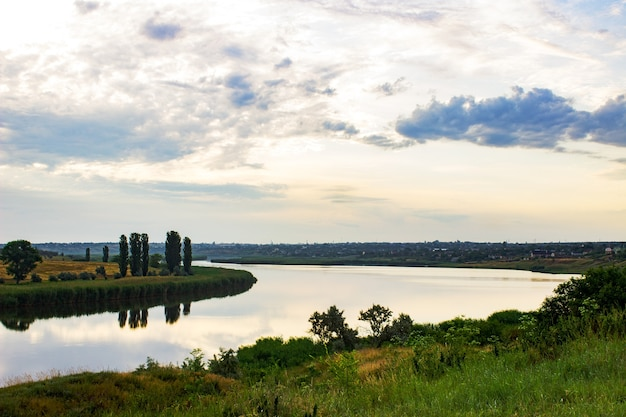 Zomeravond dageraad hemel wolken weerspiegeld op een meer van water aan de kust met groen gras en bos bomen.