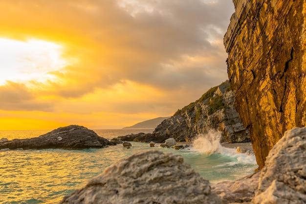 Zomeravond en het kleine strand aan een rotsachtige kust. surfspray