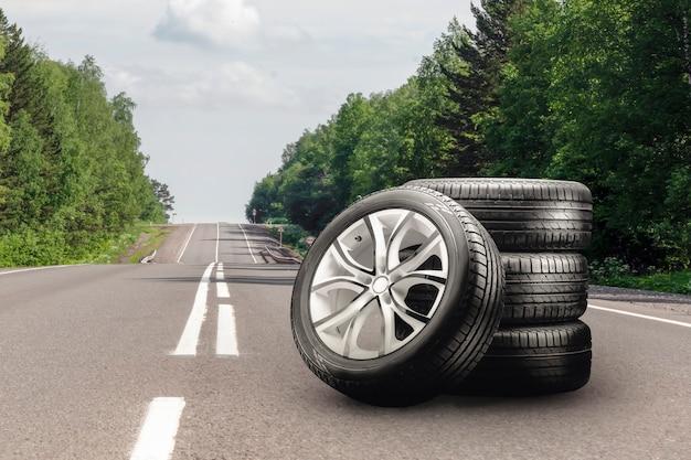Zomerbanden en lichtmetalen velgen op een asfaltweg, bandenwisselseizoen autohandel kopieerruimte auto ...