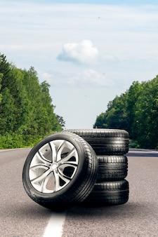 Zomerbanden en lichtmetalen velgen op een asfaltweg. bandenwisselseizoen, autohandel, kopieerruimte, . autotuning en bandenservice. verticale foto.
