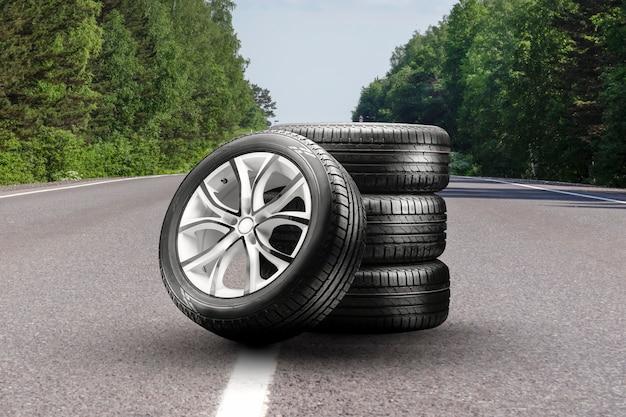 Zomerbanden en lichtmetalen velgen op een asfaltweg. bandenwisselseizoen, autohandel, kopieerruimte, vierkante foto. autotuning en bandenservice.