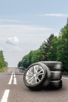 Zomerbanden en lichtmetalen velgen op een asfaltweg. bandwisselseizoen autohandel kopieerruimte vierkant...