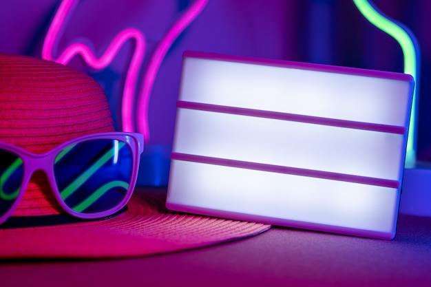 Zomerblank lichtbakje op hoed met zonnebrilreflectie neon roze en blauw en groen licht op tafel