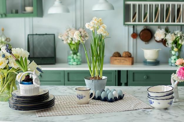 Zomerbloemen en gebruiksvoorwerpen porseleinen borden op keukentafel met paasdecor