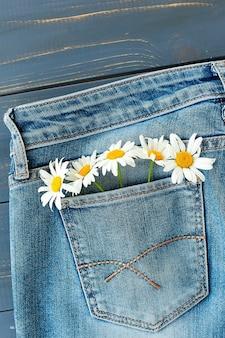 Zomerbloemen in de zak van mijn spijkerbroek op blauwe tafel