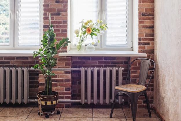 Zomerbloemen in glazen vaas op ramen in loft interieur