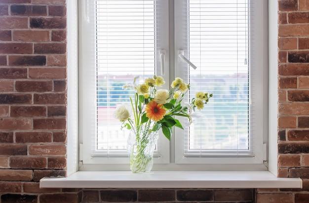 Zomerbloemen in glazen vaas op windowsiil