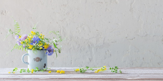 Zomerbloemen in oude beker op witte achtergrond