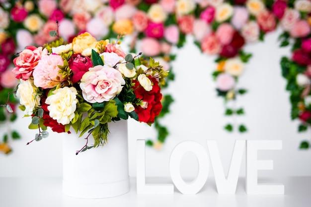 Zomerbloemen in ronde doos en houten woord liefde over lente achtergrond