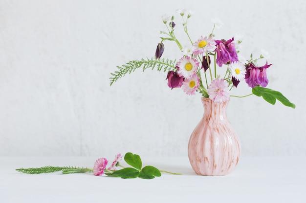 Zomerbloemen in roze vaas op witte ondergrond