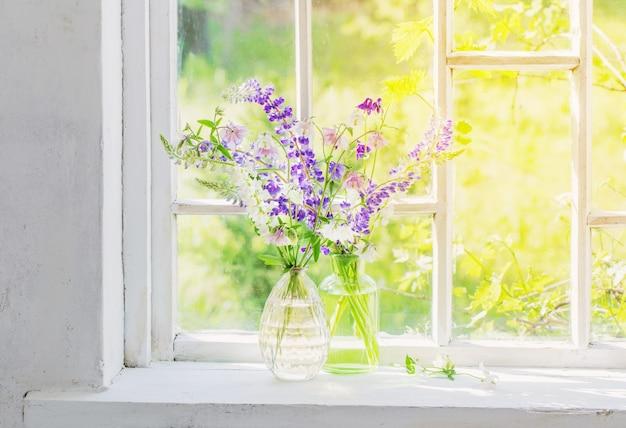 Zomerbloemen in vaas op vensterbank in zonlicht