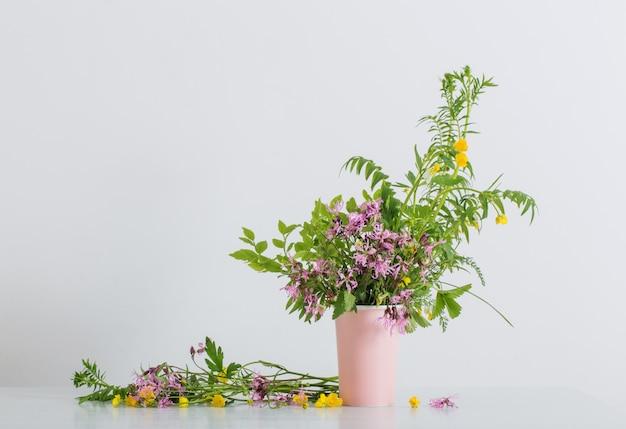 Zomerbloemen in vaas op witte achtergrond