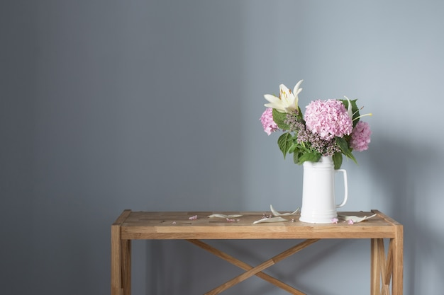 Zomerbloemen in witte kan op houten plank