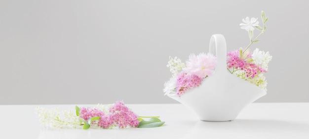 Zomerbloemen in witte keramische mand