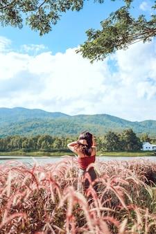 Zomerbloemen mooie jonge aziatische vrouw fantastische natuur wachten op zomerzon op weide vakantie aziatisch meisje gelukkig meisje ontspannen geniet van de herfst zonsondergang