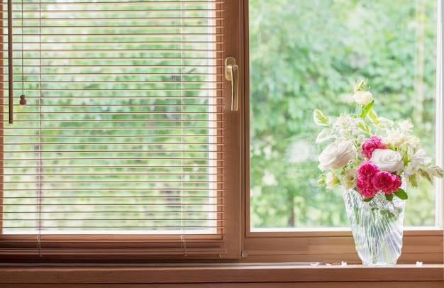 Zomerboeket in glazen vaas op vensterbank in houten huis