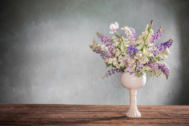 Zomerboeket in witte vaas op grijze achtergrond Premium Foto
