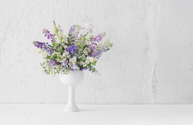 Zomerboeket in witte vaas op witte achtergrond Premium Foto