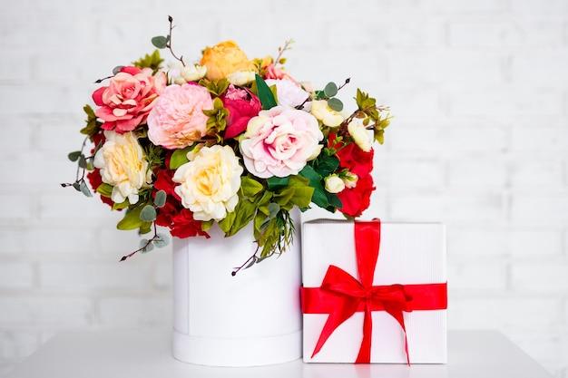 Zomerboeket van mooie bloemen en geschenkdoos op tafel over witte bakstenen muurachtergrond