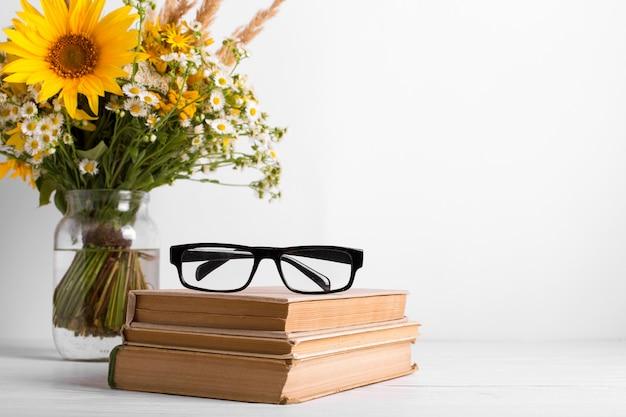 Zomerboeket van wilde bloemen in glazen vaas, oude boeken. seizoen ontwerpconcept. leraren dag concept