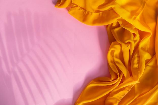 Zomerconcept. schaduw van varenblad en gele sjaal op gemakkelijke rode papieren achtergrond.