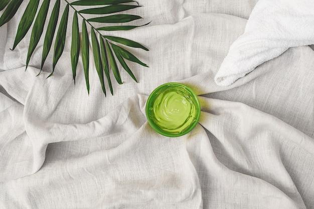 Zomercosmetica groene hydraterende gelhanddoek en palmblad op de achtergrond van linnen stof
