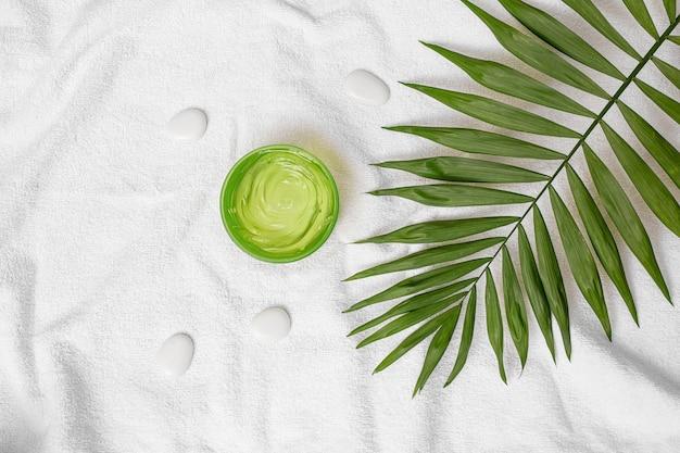 Zomercosmetica hydraterende gel groene kleur en palmblad op de handdoek en witte stenen achtergrond voor spa