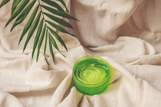 Zomercosmetica hydraterende gel van groene kleur met palmblad op de achtergrond van linnen stof