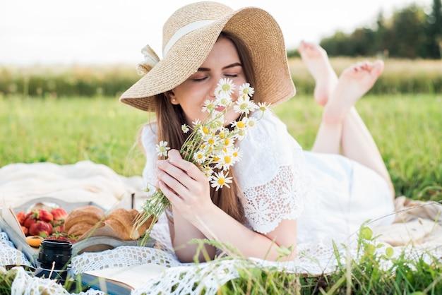 Zomerdag, picknick in het dorp. een mooi meisje met een hoed ligt op een geruite plaid. een boeket madeliefjes, bloemen in haar haar.