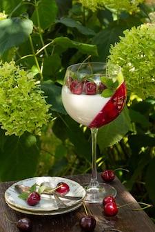 Zomerdessert in wijnglas met kersen. panna cotta met bessen in glas op tuinachtergrond.