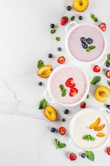 Zomerdieet gezond diner, veganistisch eten, dessert, verschillende zoete romige fruit- en bessensoepen - aardbei, perzik, bosbessen, tafelblad van wit marmer