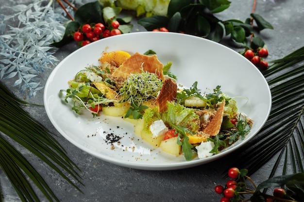 Zomerdieetsalade met bladeren van sla, watermeloen, perzik en fetakaas op een lichtblauwe achtergrond