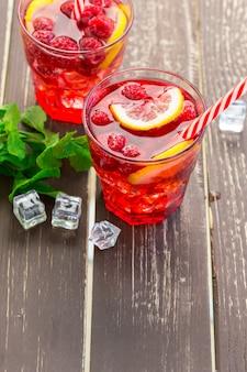 Zomerdrank met frambozen, limoen en ijs op een oude houten tafel
