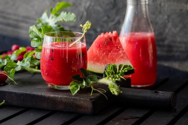 Zomerdrankje koud watermeloensap met limoen en munt op een houten plank berryfruit-smoothie
