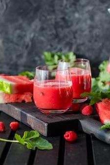 Zomerdrankje koud watermeloensap met limoen en munt op een houten plank