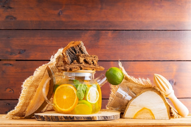 Zomerdrankje van water, citroen, sinaasappel en muntblaadjes op houten planken. lime mint ijsthee en stukjes hout. creatieve compositie