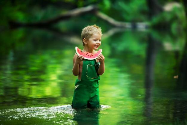 Zomerfoto in groene tonen een jongen kind staat in het meer en eet een plak watermeloen