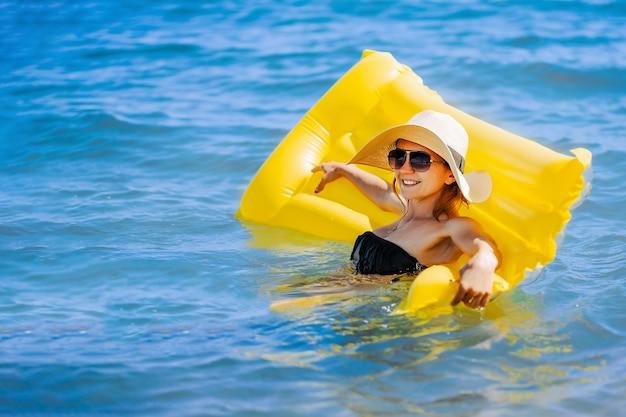Zomerfoto van een vrouw die op een gele opblaasbare matras in de oceaan zwemt met een zonnehoed van stro...