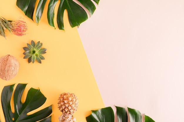 Zomerfruit en bladeren. tropische palmbladen, ananas, kokosnoot op pastel gele en roze achtergrond. plat lag, bovenaanzicht, kopie ruimte