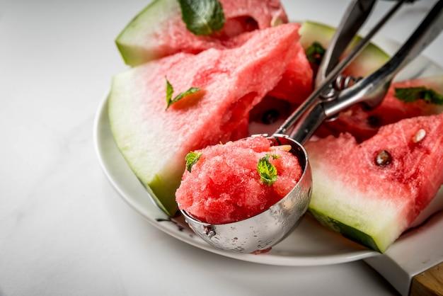 Zomerfruitdesserts, bevroren cocktails. ijs graniet van watermeloen met munt, een bolletje in een lepel voor ijs, op plaat met plakjes watermeloen.