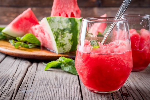 Zomerfruitdesserts, bevroren cocktails. ijs graniet van watermeloen met munt, in geportioneerde glazen, met plakjes watermeloen.