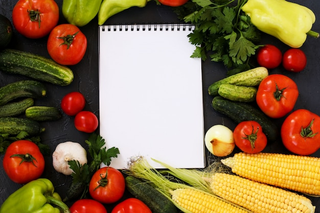 Zomergroenten: tomaten, komkommers, maïs, peterselie, paprika, uien, knoflook en courgette bevinden zich op een donkere achtergrond, bovenaanzicht