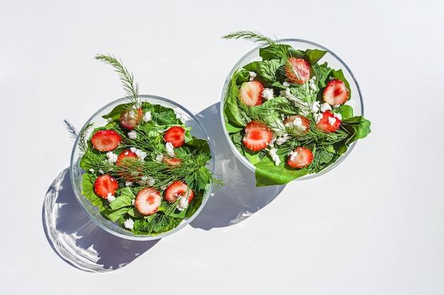 Zomergroentesalade met verse aardbeien, basilicum, mozzarella en eetbare bloemen in glazen saladekommen in de tuin op zonnige dag